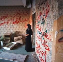 Una mujer contempla la residencia destruida de Muamar El Gadafi.