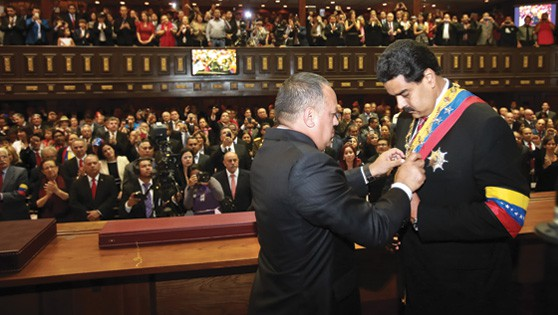 Diosdado Cabello coloca la banda presidencial a Nicolás Maduro.